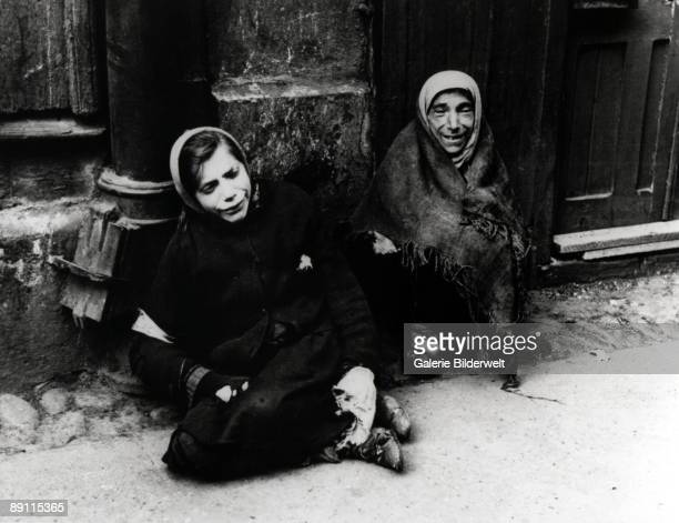 A girl and a woman begging in the Warsaw Ghetto during World War II Poland 1941
