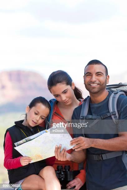 'Girl and adult hikers looking at map, Sedona, Arizona, USA'
