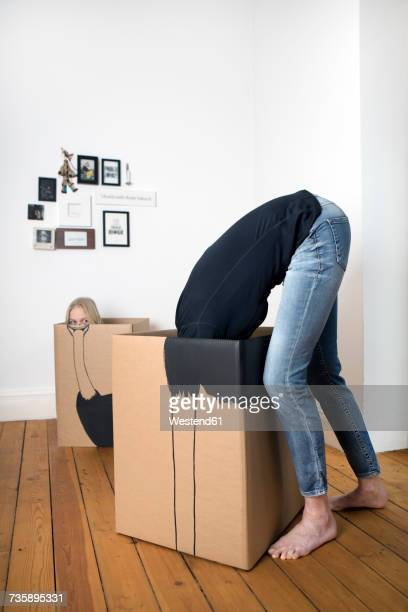 Girl and adult inside cardboard boxes painted with an ostriches
