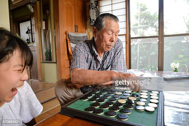 Girl and aged man playing Othello game.