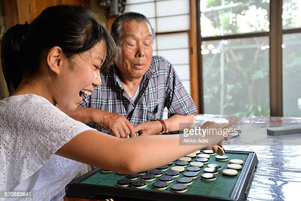 Girl and aged man playing Othello game together.