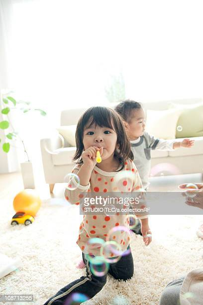 Girl and baby boy playing with bubble