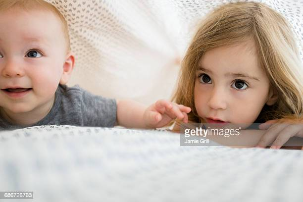 Girl (2-3) and baby brother (6-11 months) hiding under bed covers