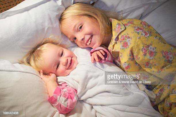 Girl and baby girl in bed, smiling