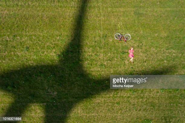 Girl and bicycle beside shadow of modern wind turbine