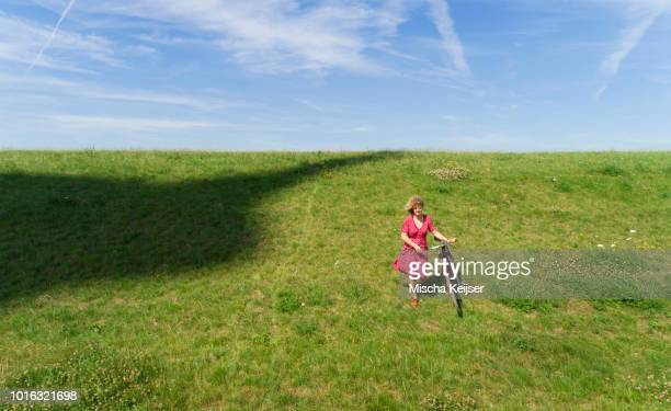 girl and bicycle beside shadow of modern wind turbine - levee stock pictures, royalty-free photos & images