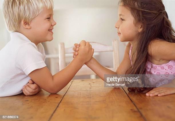 Girl and boy arm wrestling