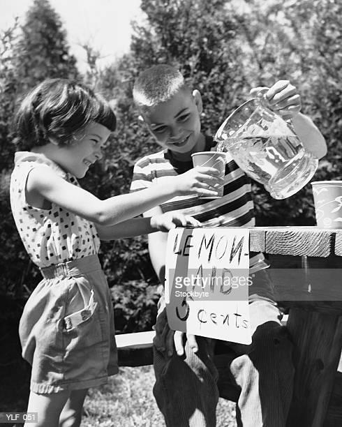 Mädchen und Jungen an Limonadenstand