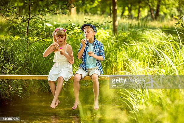 Girl and boy blowing soap bubbles above a stream