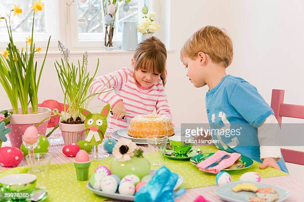 girl and boy cutting cake easter table