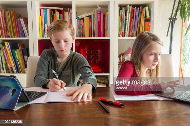 girl and boy doing her homework with tablet and laptop