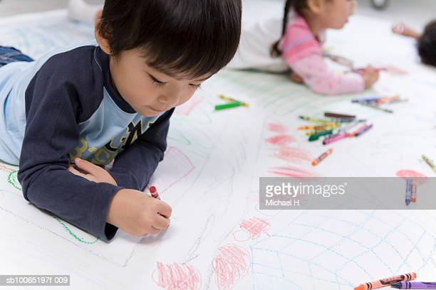 girl and boy (4-5 years) drawing on floor with crayons - 4 5 years stock pictures, royalty-free photos & images