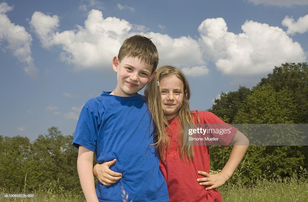 Girl and boy (8-9 years) embracing in meadow, portrait : Foto stock
