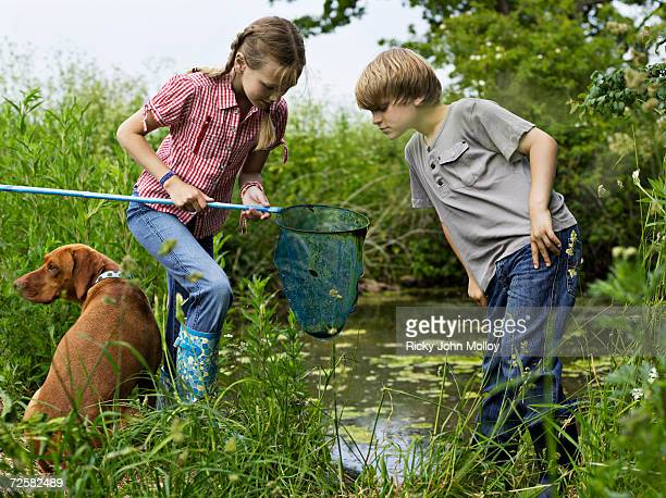 Girl (10-11) and boy (7-8) fishing in pond with brown dog