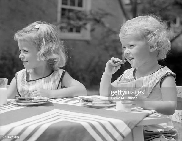girl and boy having breakfast at outside table - {{ contactusnotification.cta }} stockfoto's en -beelden