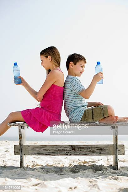 Girl and boy holding bottles of water on a beach