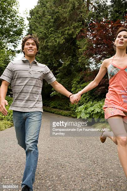 girl and boy holding hands and running