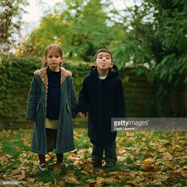Girl and boy holding hands outside, boy sticking out tongue