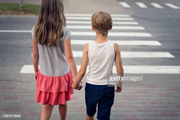 girl and boy holding hands waiting at the crosswalk - pedestrian crossing stock photos and pictures