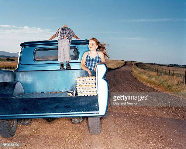 Girl (9-11) and boy (5-7) in back of parked truck