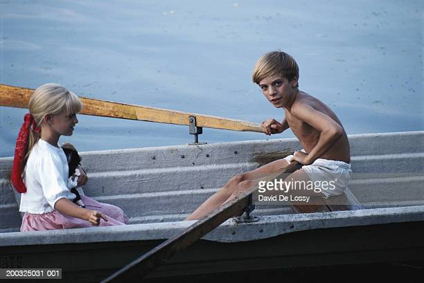 Girl (4-5) and boy (8-11) in boat, boy rowing, elevated view
