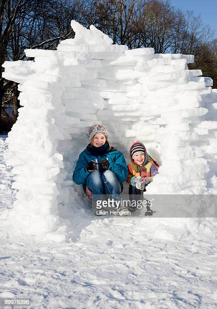 girl and boy in igloo in the snow - igloo stock pictures, royalty-free photos & images