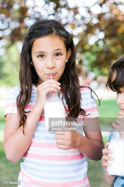 Girl (10-11) and boy (6-7) in park drinking milk