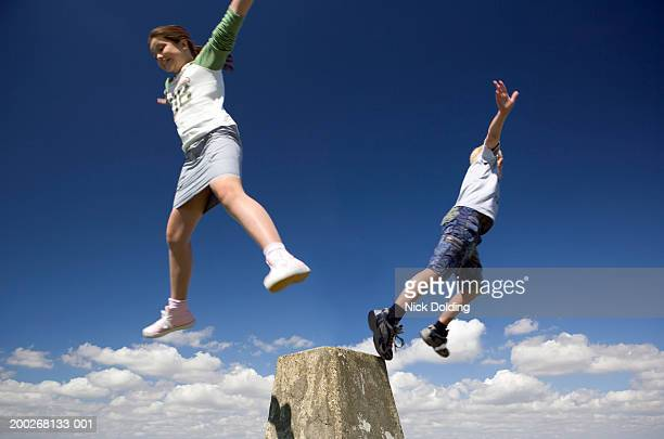girl and boy (8-11) jumping off of concrete post, low angle view - legs apart stock photos and pictures
