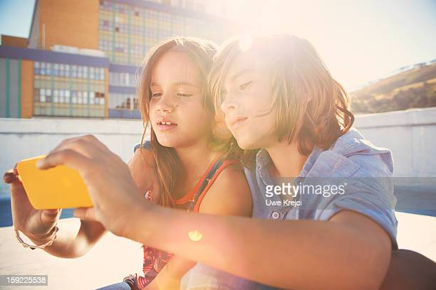 girl and boy (8-10) looking at smart phone - newtechnology stock pictures, royalty-free photos & images
