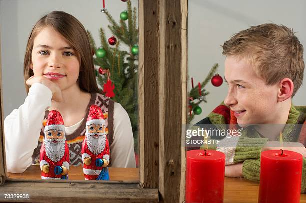 Girl and boy looking out of a window, Christmas tree in background