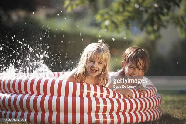 Girl and boy (4-7) lying in paddling pool