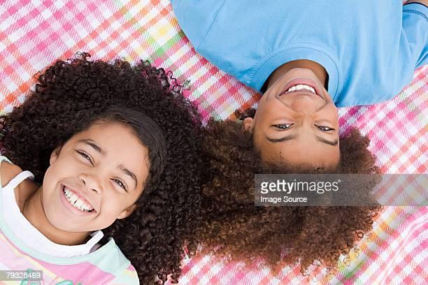 Girl and boy lying on blanket