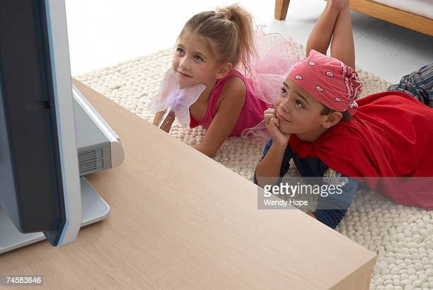 Girl (6-8) and boy (5-7) lying on floor watching television in living room, high angle view