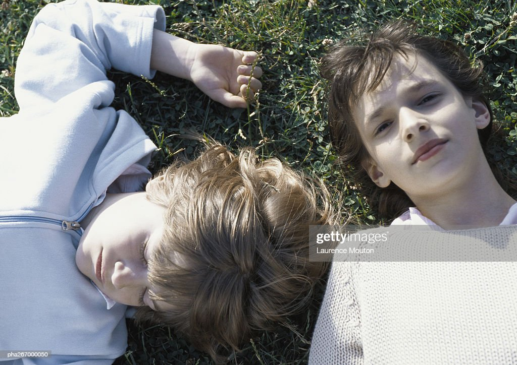 Girl and boy lying on grass : Stockfoto