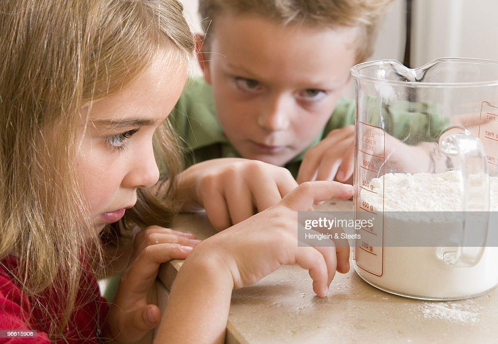 girl and boy measuring flour : Stock Photo
