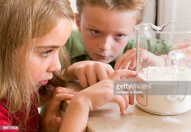 girl and boy measuring flour