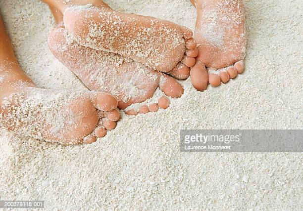 Girl (12-14) and boy (7-9) on beach, feet covered in sand, close-up