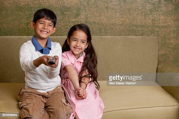 girl and boy on couch with tv remote