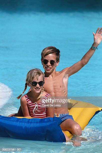 Girl and boy on pool raft