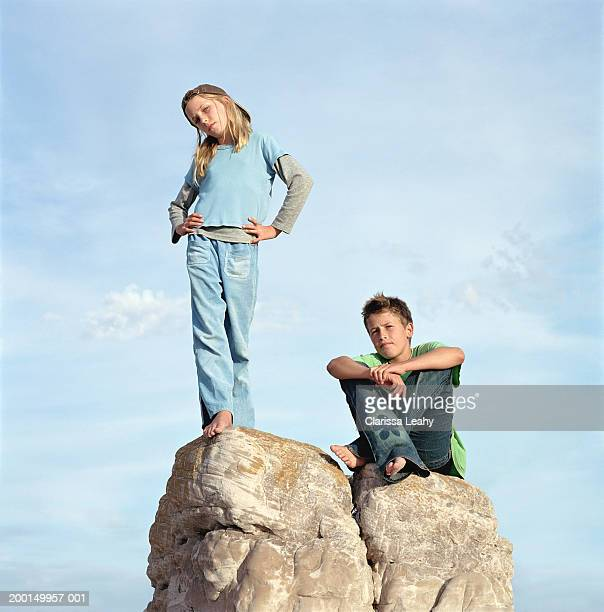 Girl and boy (11-13) on rock, portrait