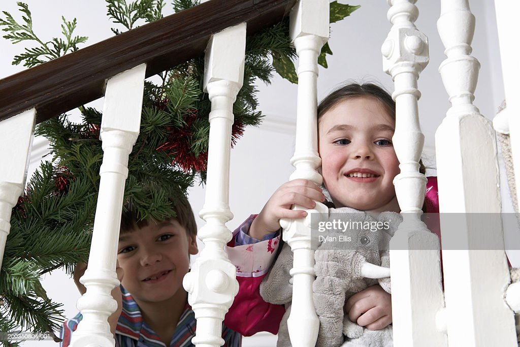 Girl and boy (5-7) on stairs, looking through bannisters, smiling : Stock-Foto