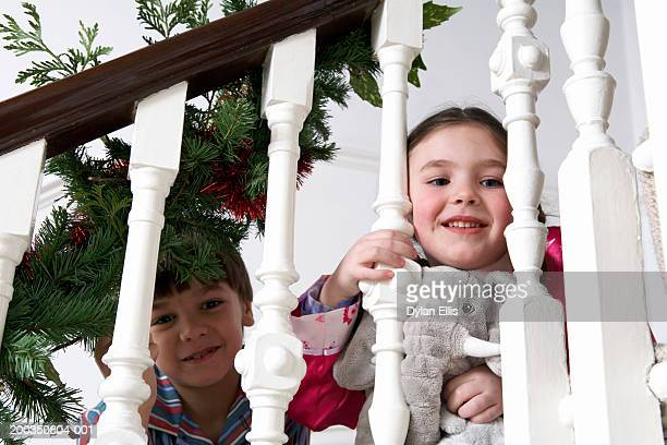 Girl and boy (5-7) on stairs, looking through bannisters, smiling