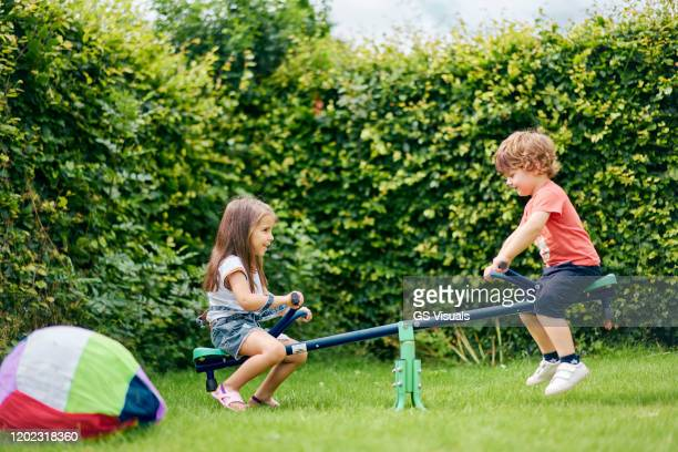 girl and boy on toy seesaw in garden - nursery school child stock pictures, royalty-free photos & images