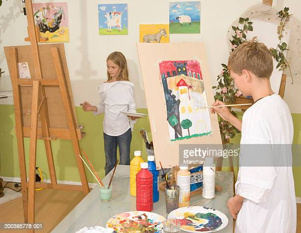 girl and boy (9-11) painting in art class - 10 11 años fotografías e imágenes de stock