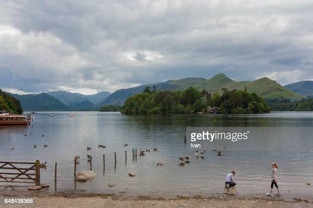 a girl and boy play near a lake - derwent water - fotografias e filmes do acervo