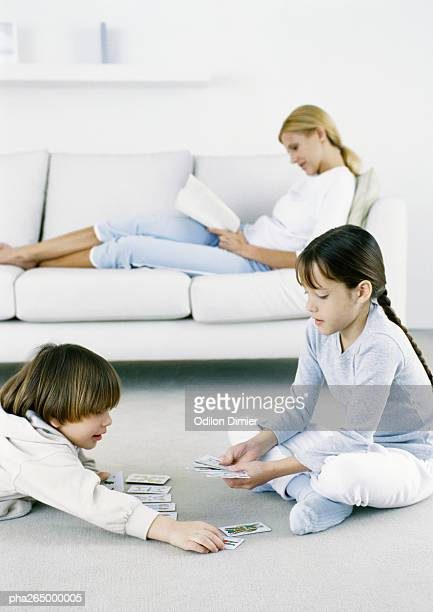 Girl and boy playing cards on floor, woman sitting on sofa reading in background
