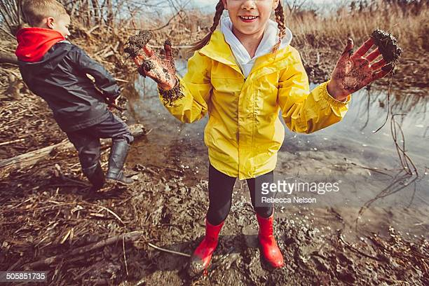 Girl and boy playing in mud