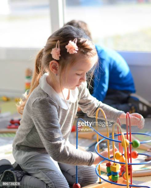 Girl and boy playing in the playroom with education toys