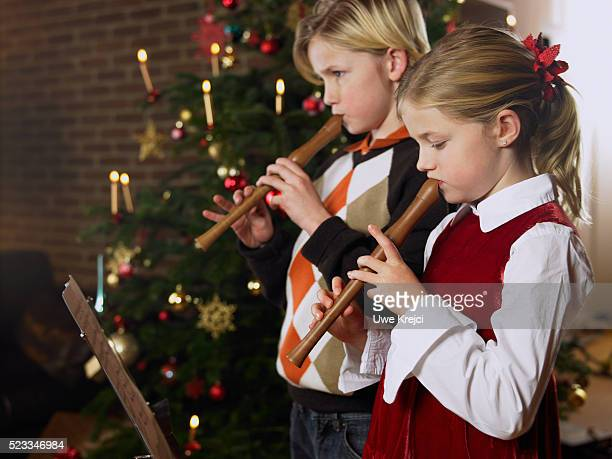 Girl and Boy Playing Recorder in Front of Christmas Tree