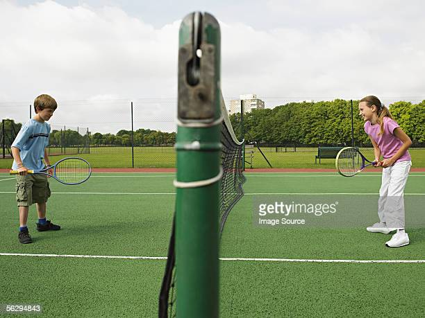 girl and boy playing tennis - face off sports play stock photos and pictures